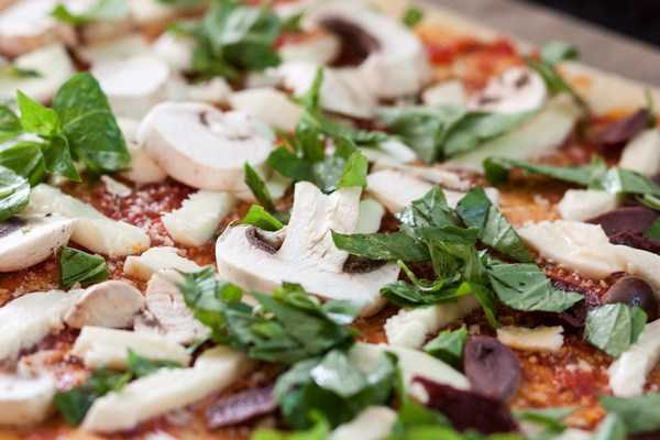Basilikum auf eine Pizza mit Tomatensauce und Pilze